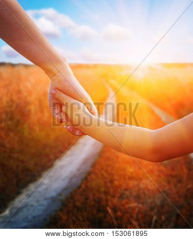 Hands of mother and daughter holding each other in field on road and sun