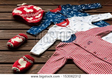 Baby Boy Clothes (sleepsuits, Knitted Hat And Mittens) On Brown Wooden Background