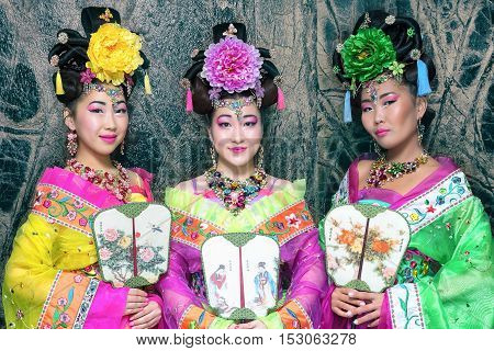 Three beautiful Chinese woman in traditional Chinese dress with fan near the marble wall