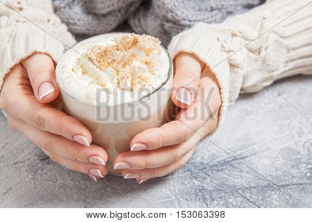 woman hands with coffee latte on a table
