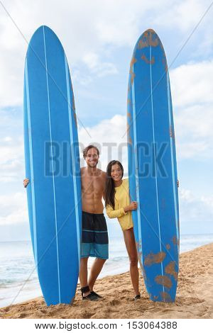 Happy young couple surfers posing with long surfboard on hawaii beach after surf class. Male surfing instructor with Asian tourist on Maui touristic beach having fun.