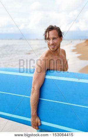 Sexy surfer surfing man with surfboard. Handsome young Caucasian male athlete holding blue surf board with wet hair on summer beach sport holiday. Sports travel destination. Surfing lifestyle.