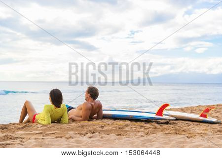 Couple surfers relaxing after surfing on hawaiian beach. Two people lying down on sand beach at sunset next to surfboards after a surf class on Kaanapali beach in Maui, Hawaii island, USA.