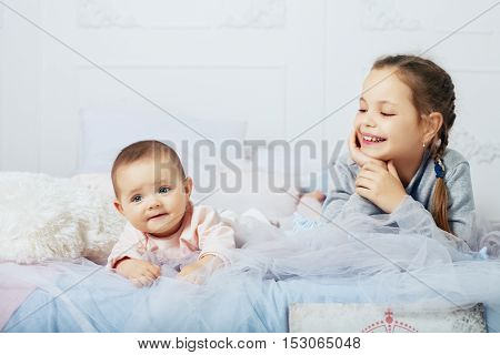children sisters lay on the bed. The concept of family and childhood.