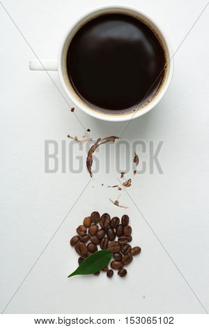 Cup of coffee with grains, green leaf and stain on white background, closeup