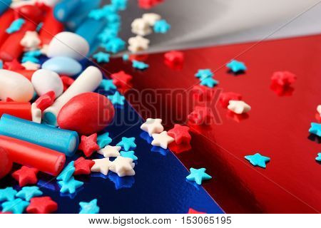Scattered colorful small candies on colorful shining background
