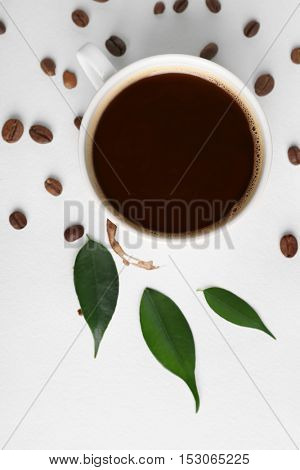 Cup of coffee with grains, green leaves and stain on white background, closeup