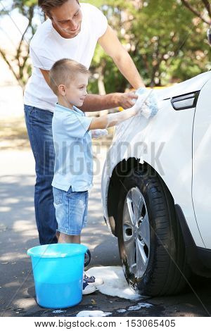 Father and son washing car on street