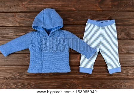 Babies Blue Knitted Cardigan And Striped Pants On Wooden Background. Baby Clothes