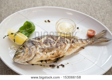 dorado grilled on a plate served with a slice of lemon and sauce