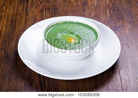 on the table a plate of spinach soup with quail egg top view
