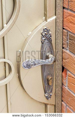 on a metal door Forged door handle with a modern lock.