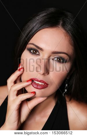 Portrait of beautiful woman with trendy makeup on black background