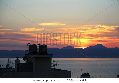 Beautiful sunset on the sea and top of roofs with antennas Balearic Islands Mallorca (Majorca) Spain