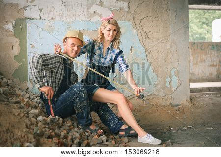 Portrait of a young man and woman in overalls with tools in a newly built house. Concept of construction and home repair.