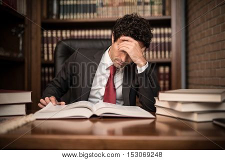 Portrait of a tired businessman reading a book