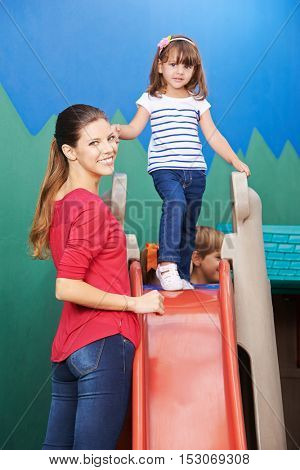 Mother standing with daughter on slide in a nursery