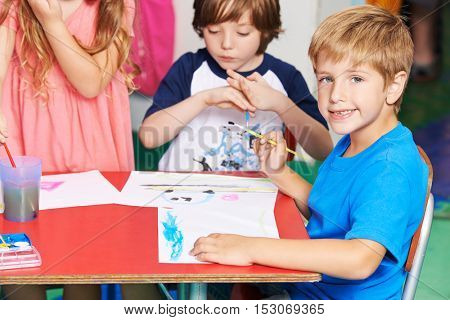 Boy painting image with water color and brush in elementary school