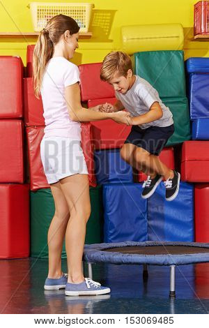 Boy jumping on trampoline in gym with help of PE teacher