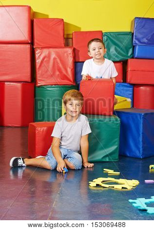 Two boys playing together in a preschool gym
