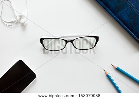 White office desk with glasses, pencils, earphones and mobile on it. Business concept, lay flat, copy space