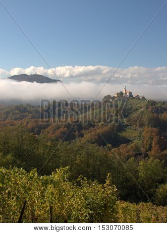 Landscapes from the top of hill from travel to Slovenia: forests, mountains, autumn background, sky, clouds, church - on sunny day