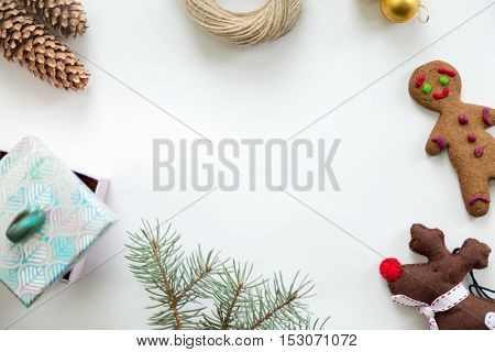 Flat view of Christmas decoration, cones, fir tree branch, gift box, twine, glass ball, ginger man, Rudolph the Red Nosed Reindeer toy. Space for a text or design in the middle. Christmas concept, copy space