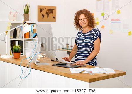 Middle age designer working on a desktop at her office