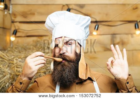 Funny man chef cook or baker with beard and moustache in hat toque with wooden spoons and ok hand gesture stands on straw bales on rustic background
