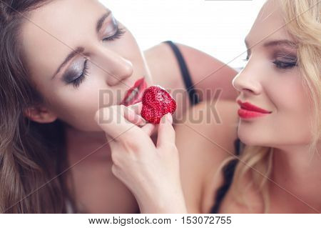 Sexy woman feeding lesbian lover with strawberry closeup