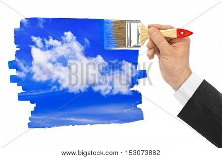 Hand with paintbrush drawing sky isolated on white background