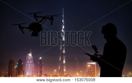 Man handling drone with modern Dubai city on background