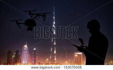 Man handling drone with modern Dubai city on background