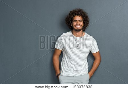 Portrait of happy young man standing against grey background. African man with hands in pocket leaning against grey wall. Multi ethnic young man in casual looking at camera with copy space.