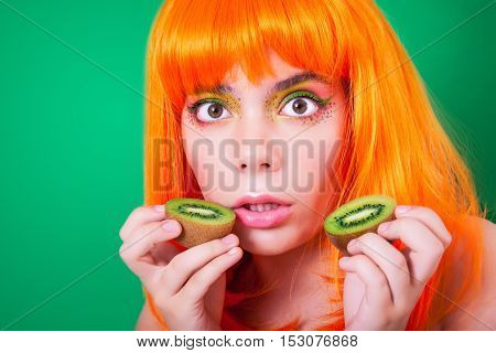 Portrait of red-haired woman in the studio close-up with kiwi.