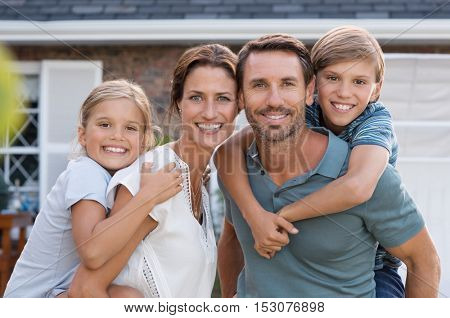 Parents giving piggyback ride to children. Happy mother and father with son and daughter looking at camera outside house. Portrait of happy couple standing carrying on shoulder their children.