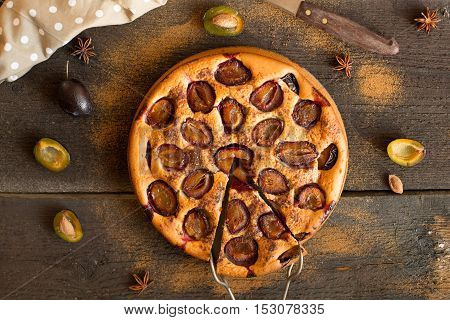 Plum cake on wooden rustic background.Overhead view