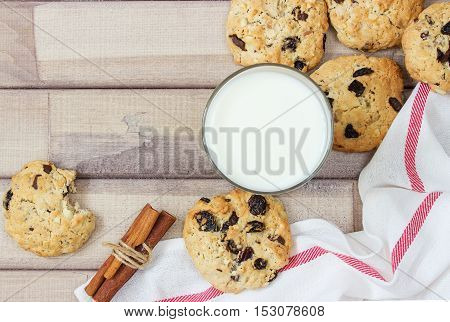 Closeup of homemade moms chocolate cookies with spices and glass of milk on wooden background