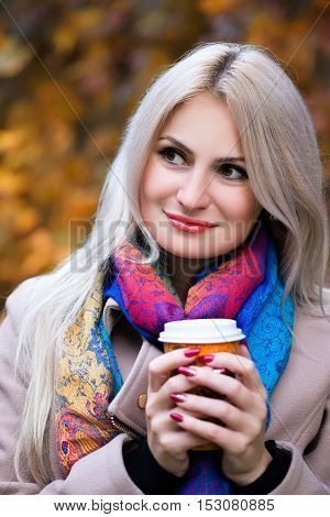 Blonde girl keeping takeaway drink in hands. Outdoors. Girl with cup of coffee in the autumn park. Fall concept - autumn woman drinking coffee in park. Beautiful young modern woman in coat. Autumn woman drinking coffee