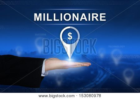 millionaire button with business hand on blurred background