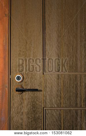 3D Rendering : illuatration of close up a wooden door details with handle and key hole