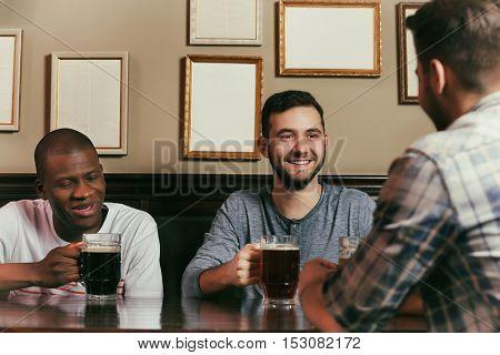 Happy friends drinking beer in pub