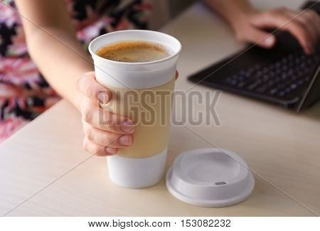 Coffee-to-go. Woman holding paper cup of coffee on table