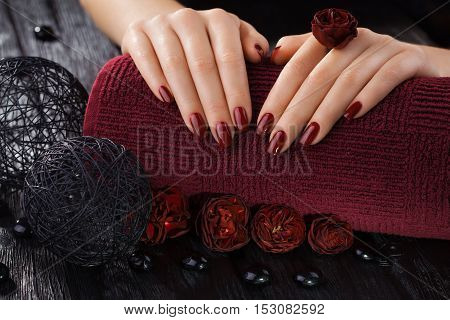 beautiful red manicure with rose flowers on the black wooden table