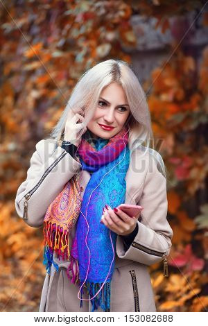 Young beautiful girl listening to MP3 player in autumn park. Beautiful autumn woman listening to music in autumn park enjoy autumn day.Beautiful young blond girl with headphones and smart phone in park in autumn. Cool young woman listening to music outdoo