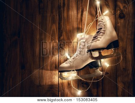 Figure skates and Christmas garland lights on old dark wooden rustic background. Winter holidays concept.