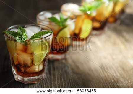 Glasses of cocktail with ice and mint on wooden background