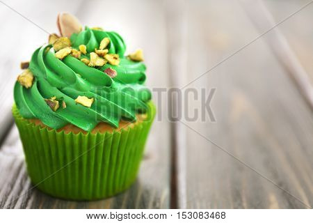 Green pistachio cupcake on wooden background