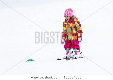 Little girl is learning to ski in ski resort. Child is skiing for the first time. Active children are happy.