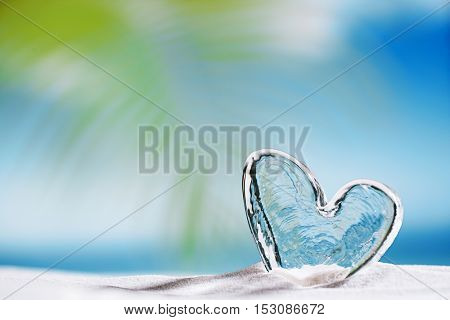 clear glass heart on white sand beach, ocean,  sky and seascape